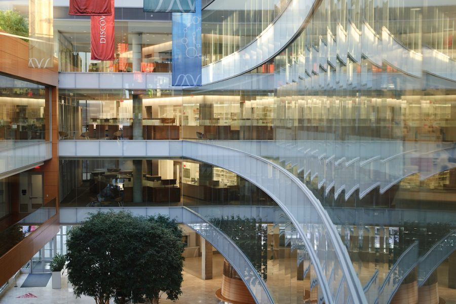 Banners hang from the ceiling as glass-paneled walls reflect a view of the Town Center atrium of the Wisconsin Institutes for Discovery